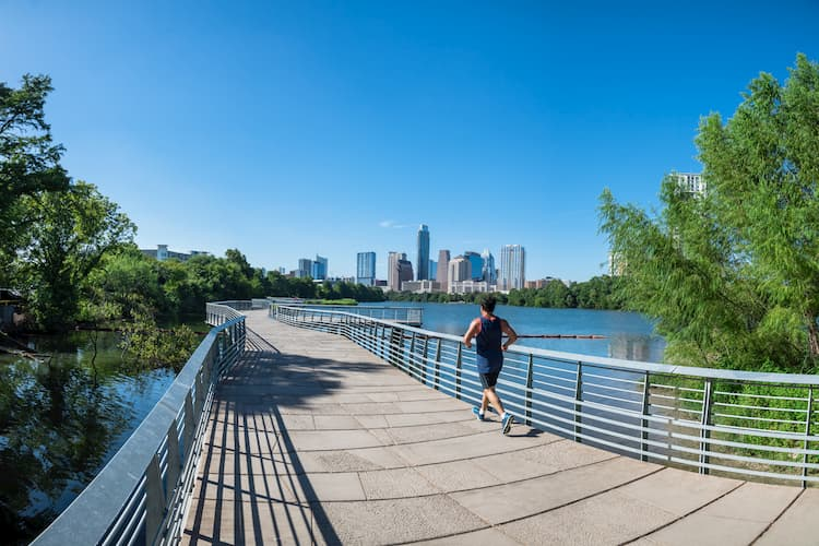 Person running outdoors with Austin skyline in the background