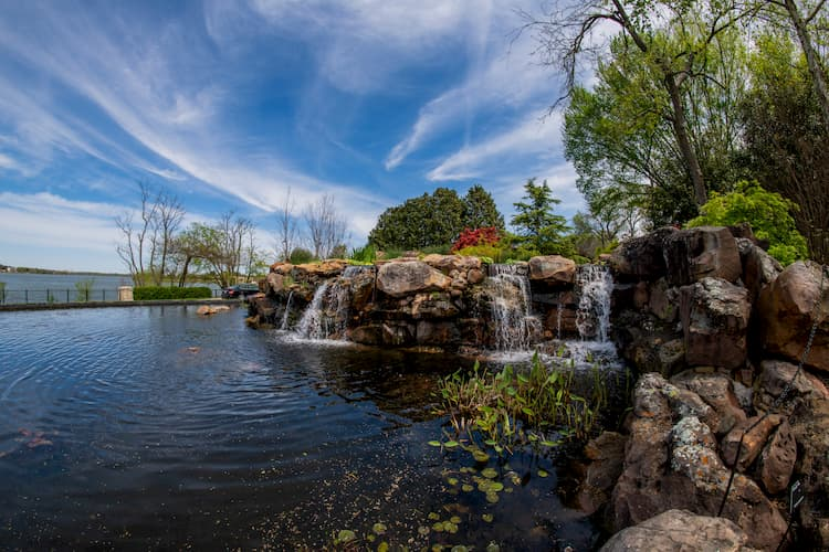 small rocks, a pond, and small waterfalls at the dallas arboretum on a sunny day