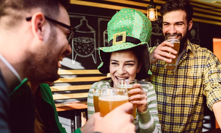 three friends toasting beer at a st patrick's day party