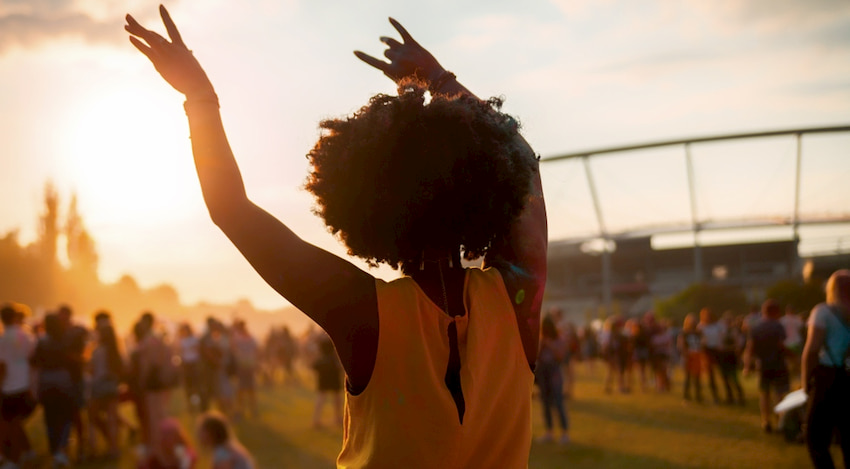 a woman dances with her arms up at an outdoor theater performance in Houston, Texas