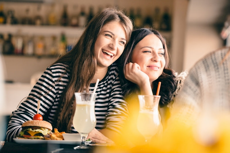 mother and daughter laugh and lean into each other during brunch in Houston, Texas