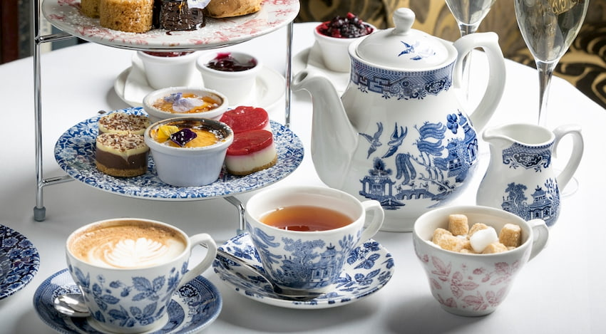 a table full of teatime accessories: a teapot, teacups, finger sandwiches and sweets