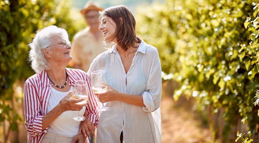 mother and daughter sip wine and walk through a vineyard outside of Houston, Texas
