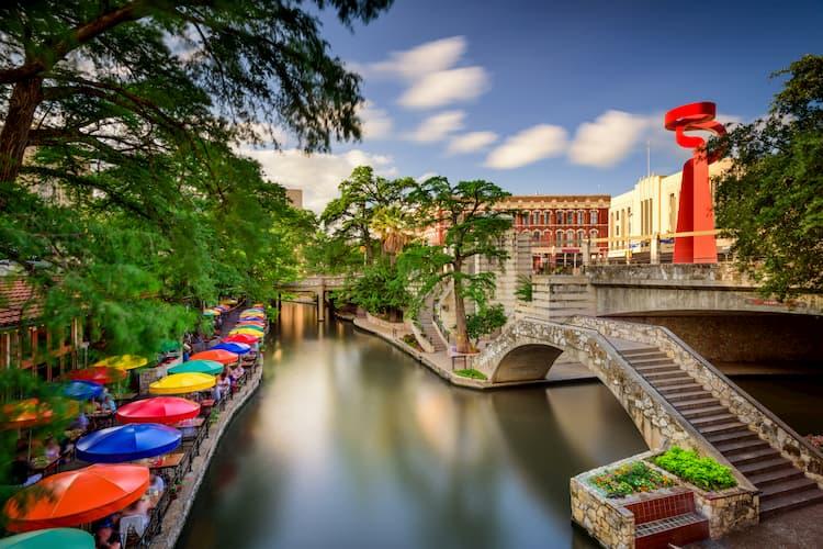 san antonio's river walk, complete with a stone bridge and colorful umbrellas