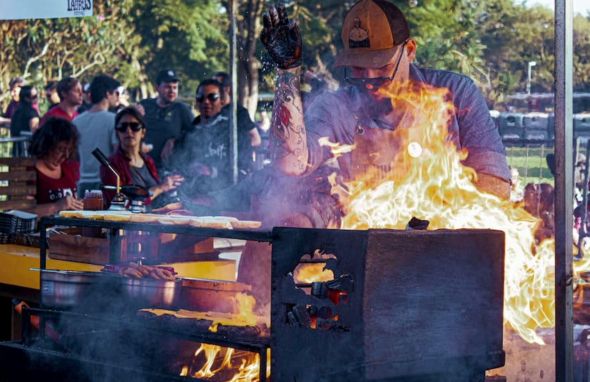 a chef seasons meat on a grill at Hot Luck Festival in Austin, Texas