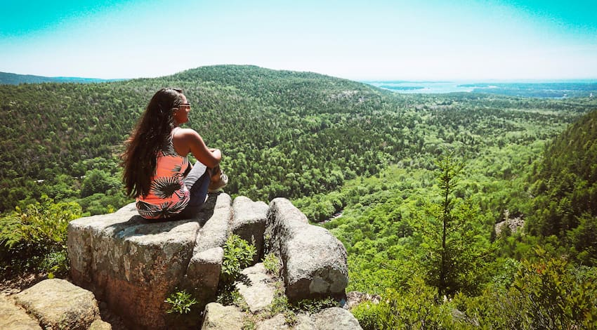 woman admires the greenery and views on top of Enchanted Rock near Austin, Texas