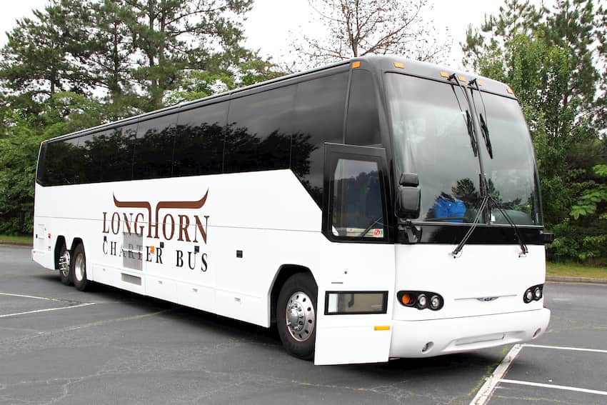 a charter bus from Longhorn waits in a parking lot
