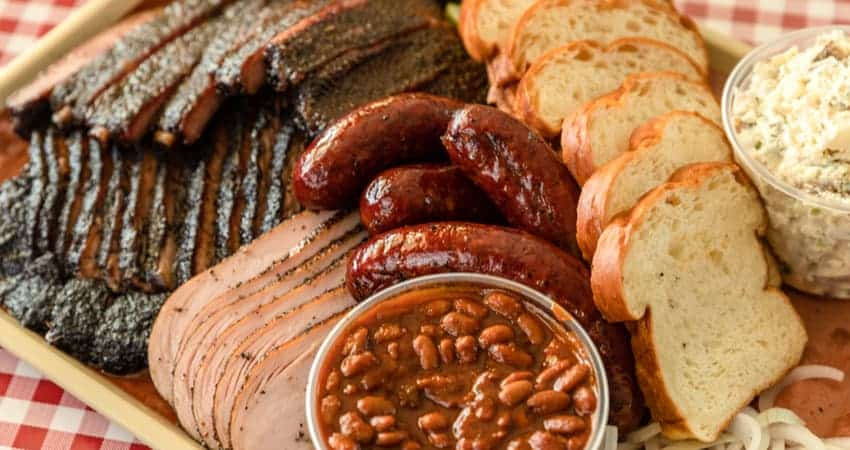 a plate filled with beans, sausages, brisket, and other texas bbq