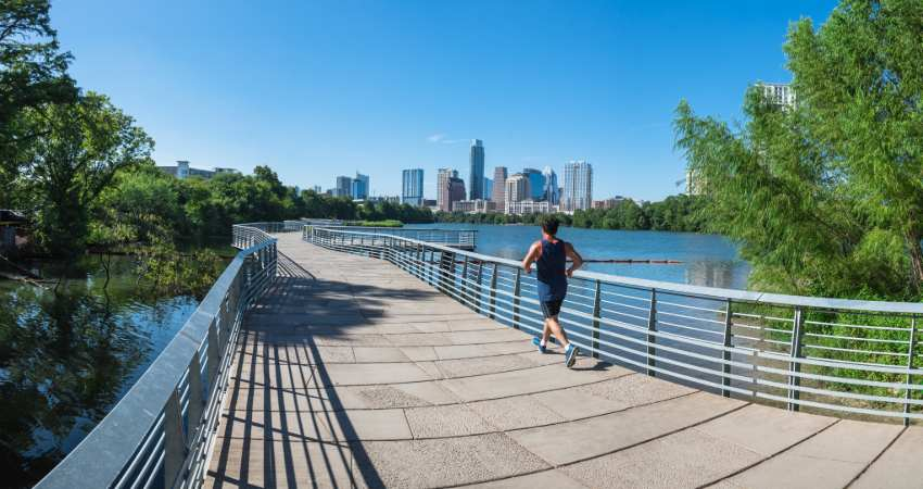 a jogger runs by on the boardwalk overlooking Lady Bird Lake in Austin