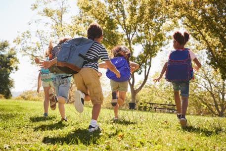 a group of children with backpacks run in a park