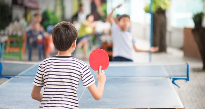 Two children playing ping pong