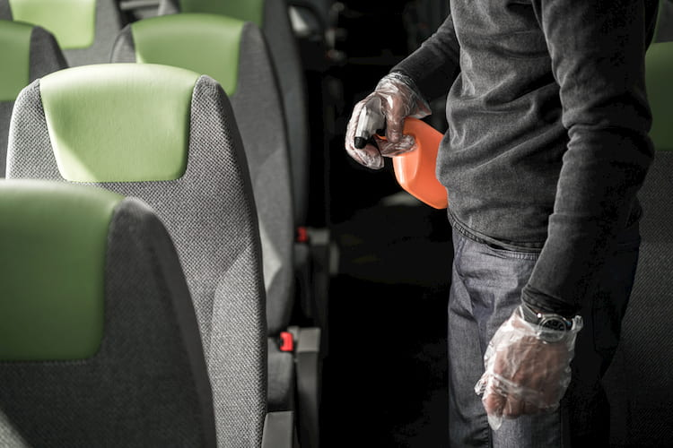 a man spraying disinfectant on a bus armrest