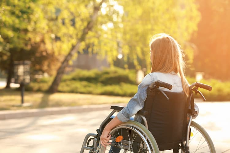 Teenage girl using wheelchair outdoors