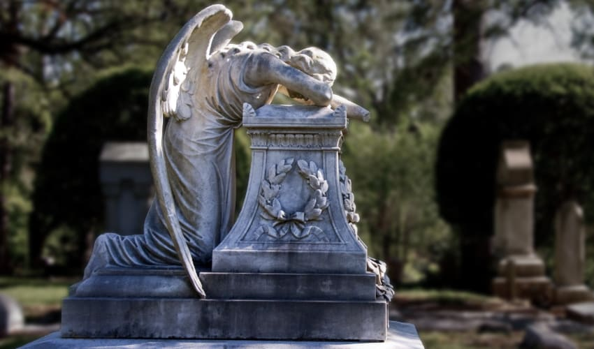 A marble angle sculpted in a crying pose on a grave at Glenwood Cemetery in Houston