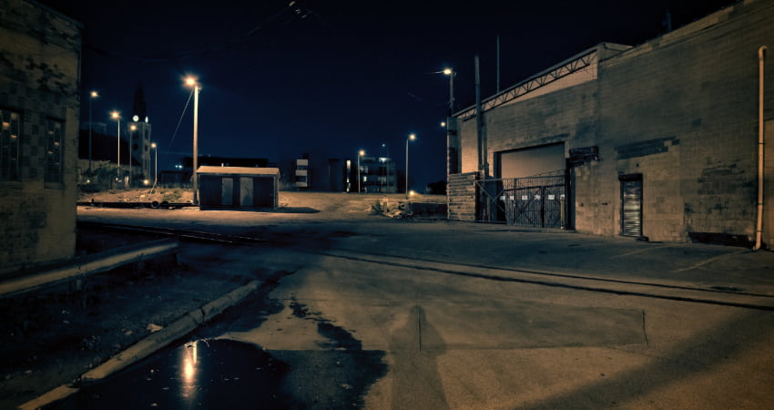 The exterior of an abandoned warehouse at night