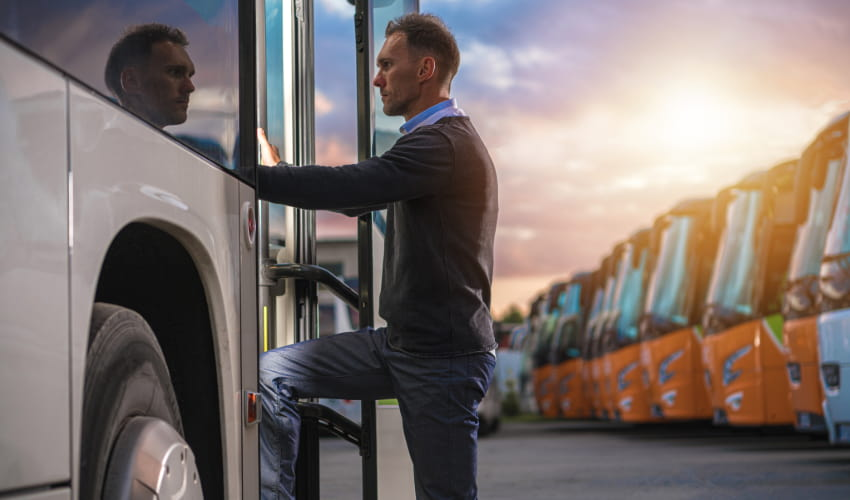 A man enters a charter bus entrance, with a sunset and a row of orange charter buses visible in the background