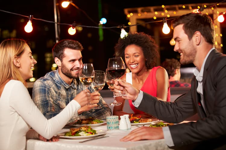 Friends having dinner on rooftop at night