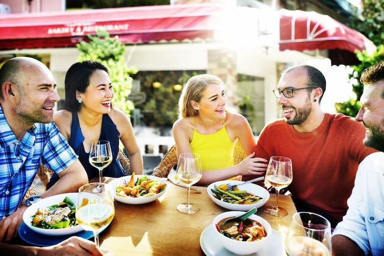 Two couples eating outside and laughing