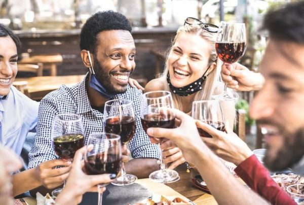 People clinking glasses of wine outside with masks lowered