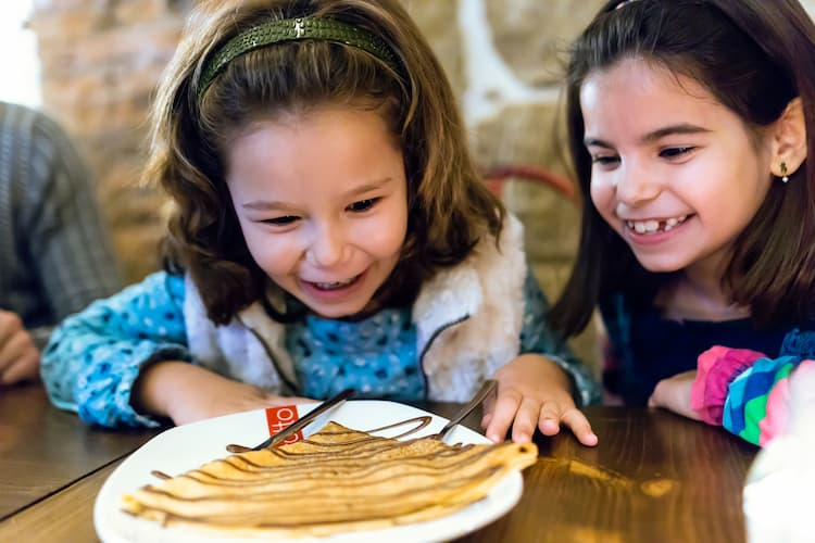 Two young girls smiling over crepe