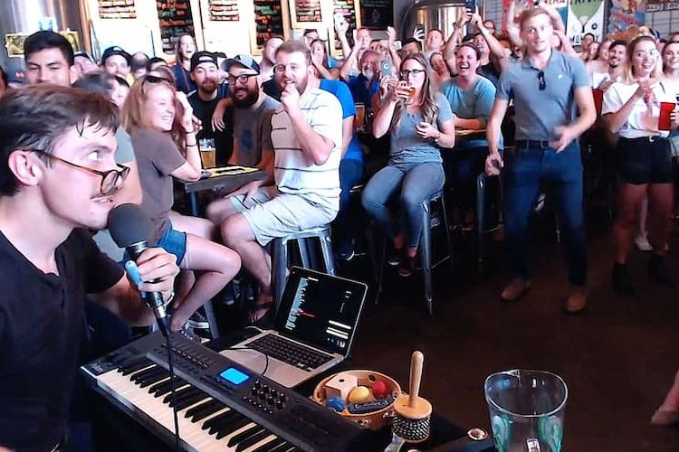 Man performs live music on keyboard at Braindead Brewing