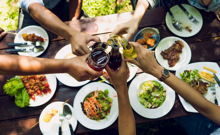 friends cheers their drinks over a table full of food