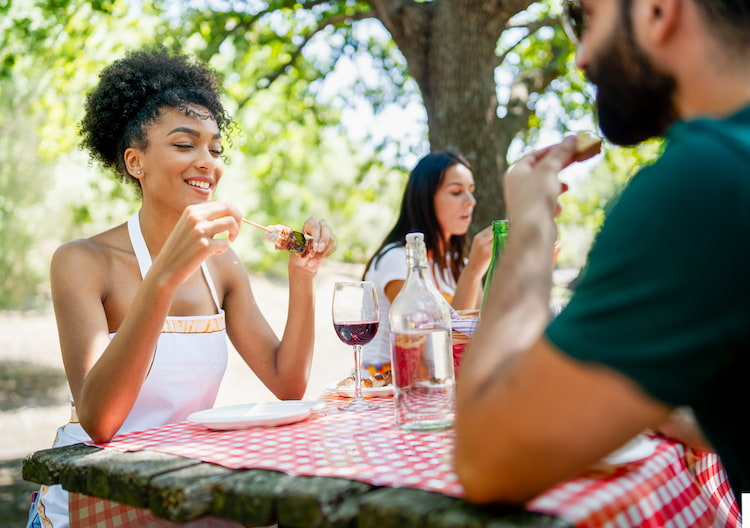 friends smile while they eat around an outdoor table