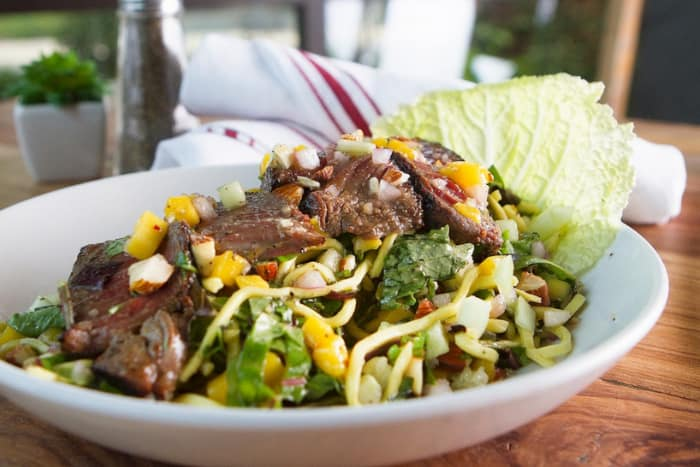 a bed of greens with a thinly-sliced steak on top