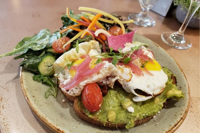 avocado toast topped with an egg, pickled red onions, and greens