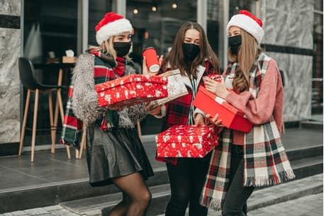A group of friends in holiday attire and masks holding gifts