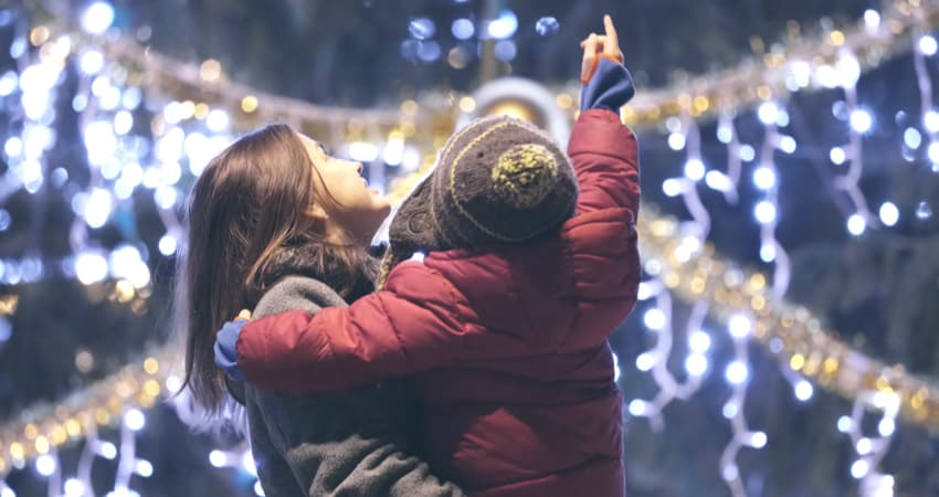 A child being held by an adult while looking up at holiday lights