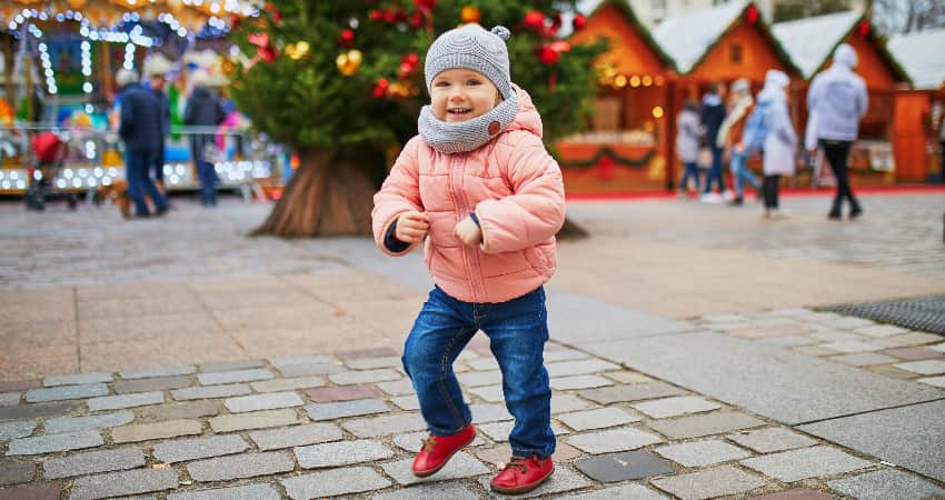 A small child in a hat and thick coat smiles and plays in a holiday street festival