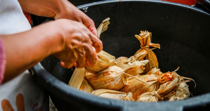 A woman places hand-made tamales in a bowl