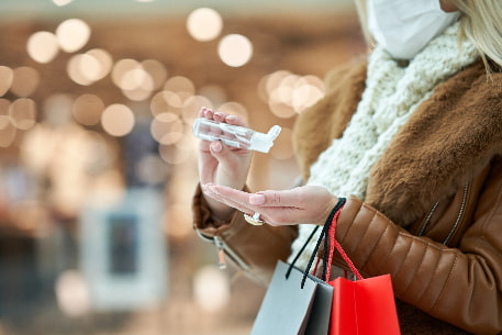 A woman sanitizes her hands while holiday shopping
