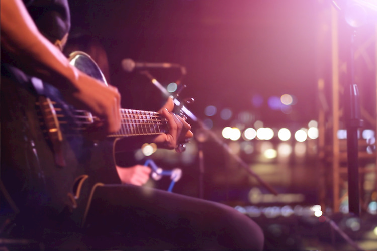 a man plays his guitar on the stage of an Austin live music venue