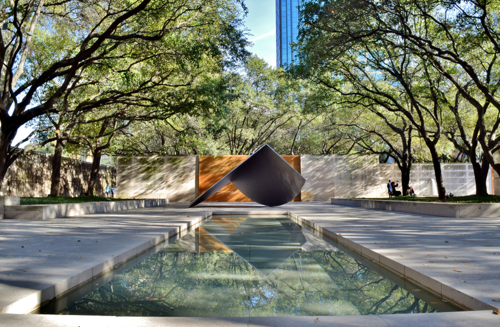 an angular art piece outside of a Dallas museum, with a reflecting pond beneath it